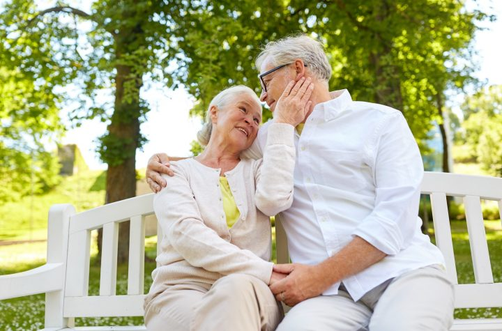 happy senior couple hugging in city park