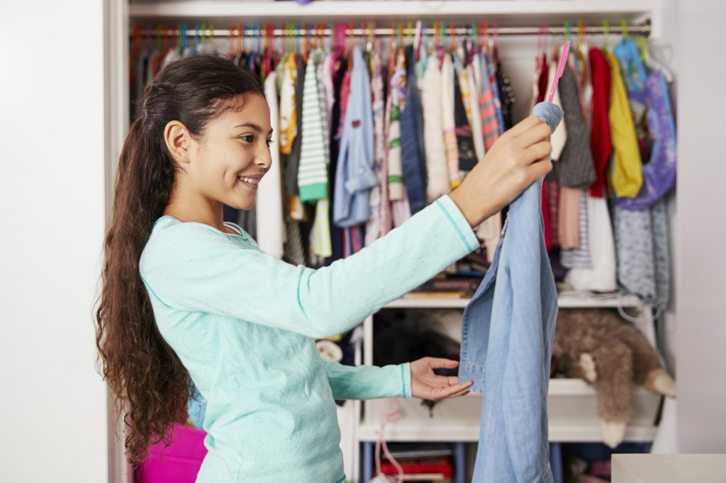 Young Girl In Bedroom Choosing Clothes From Closet
