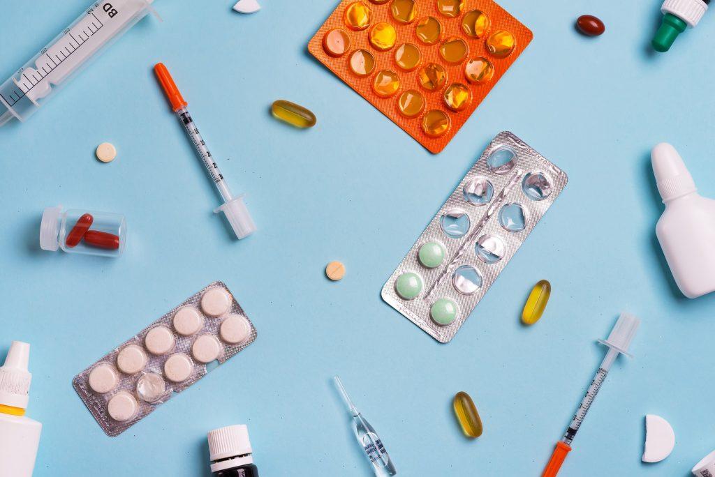 Syringes and pills on a blue background. Medicine background