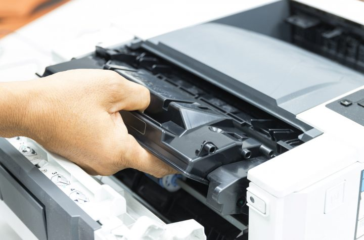 Technicians replacing toner in laser printer concept office supplies repair