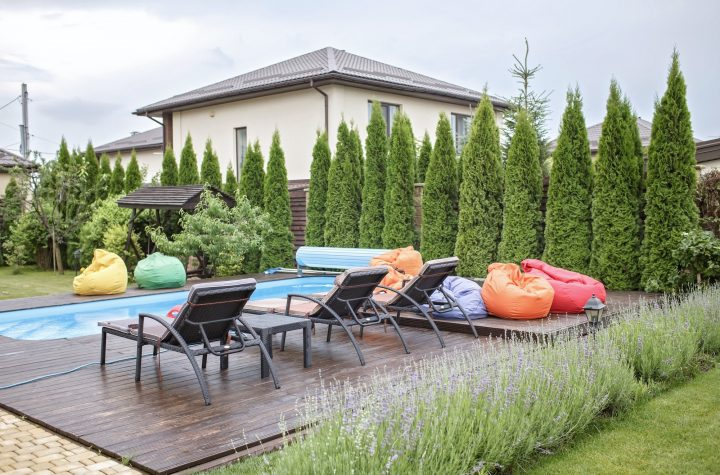 Spa area at backyard of home at summer, swimming pool, bright colorful soft chair, happy vacation