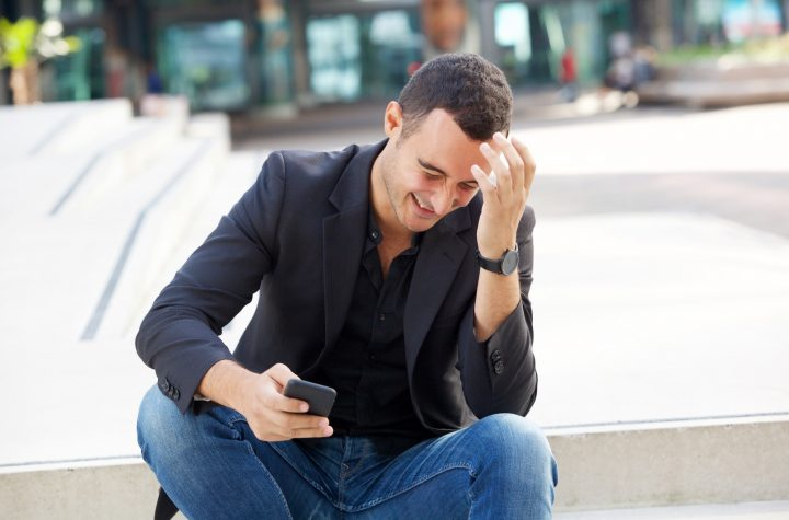 happy man laughing with cellphone outside